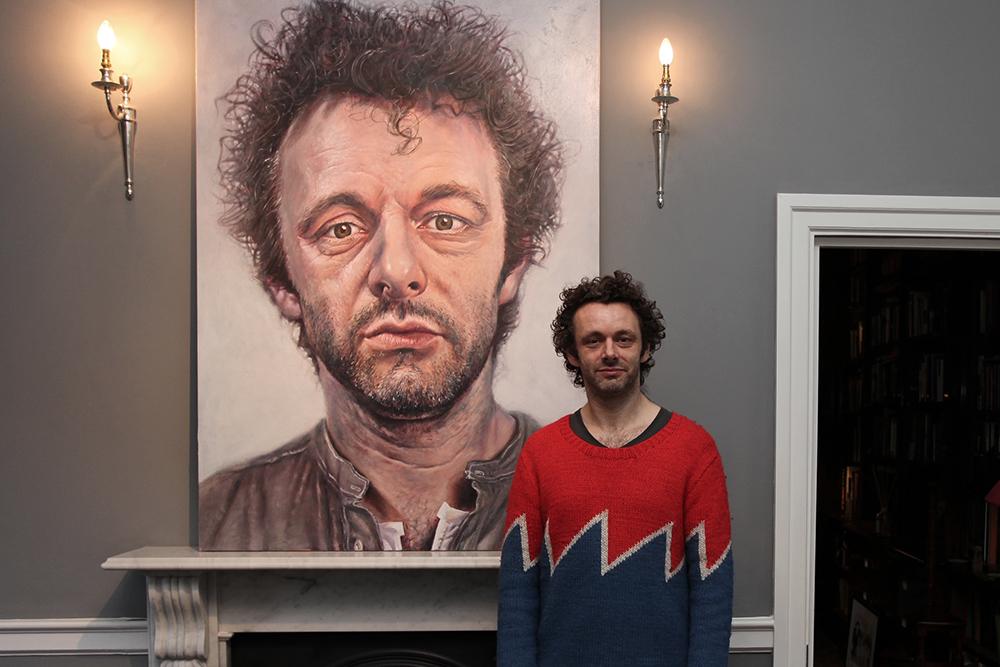 Michael Sheen standing beside Derren Brown's portrait of him